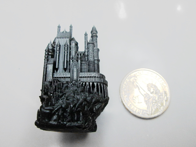 Photograph of a small 3d printed castle model with a coin as size comparison.